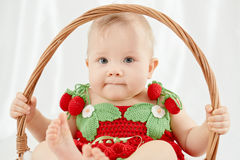 Little girl dressed in knitted strawberry suit sitting in wicker basket Stock Photos