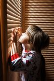 Little girl dressed in the pajama is hiding in the closet with wooden doors stock photography