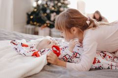 Little girl dressed in pajama is looking at her tiny brother lying on the bed in the cozy room with New Year`s tree stock photos