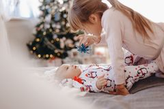 Little girl dressed in pajama is looking at her tiny brother lying on the bed in the cozy room with New Year`s tree royalty free stock photography