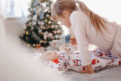 Little girl dressed in pajama is looking at her tiny brother lying on the bed in the cozy room with New Year`s tree royalty free stock photos