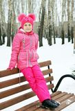 Little girl dressed in pink clothes sitting on the wooden bench in winter Royalty Free Stock Image