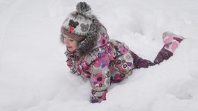 Little girl dressed in pink is the shoe, a bright jacket and cap with a pompon fooling around in the snow. She loves stock footage