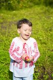Little girl dressed in Romanian traditional blouse named ie laughing outdoors