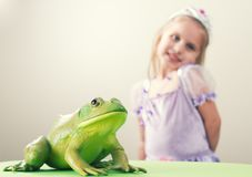 Princess and Frog Concept. A little girl dressed up as princess with a frog Stock Photo