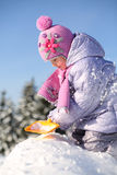 Little girl dressed in warm clothes digs with shovel and sits Stock Photography
