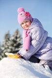 Little girl dressed in warm clothes with shovel sits on pile Stock Image