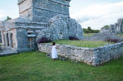 Little girl dressed in white approaches an iguana inside the May stock image