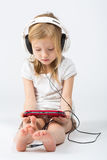 Little girl dressed in white with headphones playing. The gaming device Stock Photos