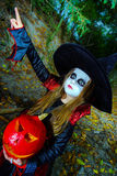 Little girl dressed in witch costume in Halloween forest Stock Photography