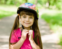 Little girl dresses a bicycle helmet Stock Images