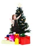 Little girl dresses up Christmas tree Stock Image