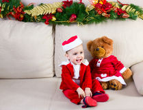 Little  girl dressing a New Year's costume with teddy bear sitti. Little cheerful girl in a New Year's outfit playing with teddy bears sitting on decorate sofa Stock Photography