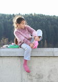 Little girl dressing up socks. Hairy little girl dressing up a pink sock while sitting on concrete wall Stock Photo