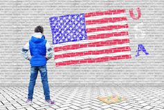 Little girl drew on a gray brick wall the USA flag Stock Photography