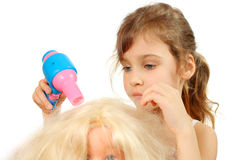 Little girl dries doll hair by toy hair dryer Royalty Free Stock Photo