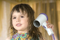Little girl dries hair Royalty Free Stock Images