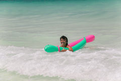 Little girl drifting in the ocean waves Stock Image