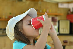 Little girl drink from cup Stock Image
