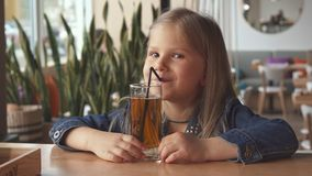 Little girl drink some flavored water at the cafe stock images