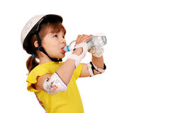 Little girl drink water. Little girl with protective gear drink water stock photography