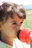 Little Girl Drinking. From a cycling bottle Royalty Free Stock Image