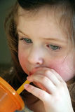 Little girl drinking. From a straw Royalty Free Stock Image
