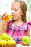 Little girl drinking apple juice Stock Images