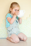 Little girl drinking from a big white cup Royalty Free Stock Image