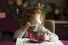 Little girl drinking from a big white cup Stock Photo
