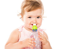 Little girl is drinking from bottle. Isolated on white background Royalty Free Stock Images