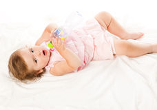 Little girl is drinking from bottle. Isolated on white background Royalty Free Stock Photos