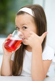 Little girl is drinking cherry juice. Showing thumb up gesture Stock Image