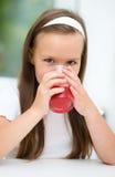Little girl is drinking cherry juice. Using straw Stock Photo