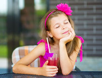 Little girl is drinking cherry juice. Using straw while sitting on terrace Stock Photos