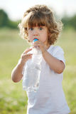 Little girl drinking clean water from plastic Royalty Free Stock Image