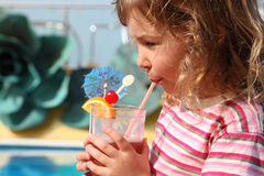Little girl drinking cocktail with fruits Royalty Free Stock Photos