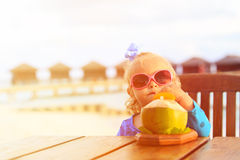 Little girl drinking coconut cocktail on beach Stock Images