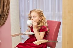 Little girl drinking coffee. Stock Images