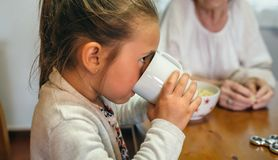 Little girl drinking a cup of milk. With her grandmother Royalty Free Stock Photos