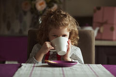Little girl drinking from a cup Royalty Free Stock Image