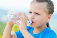 Little girl drinking fresh water from bottle Royalty Free Stock Image