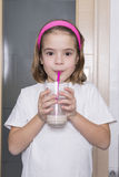 Little girl drinking a glass of milk. Little girl drinking a glass of chocolate milk with a cane pink Stock Images
