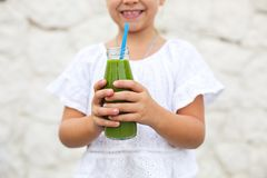 Little girl is drinking green fresh juice using straw outdoors. Close up stock photo