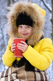 Little girl drinking hot tea in winter in cold weather. Stock Photos
