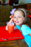 Little Girl Drinking Icy Juice in Cafe Royalty Free Stock Image