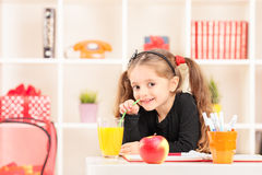 Little girl drinking a juice at home Royalty Free Stock Image