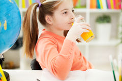 A little girl drinking a juice at home red-haired Royalty Free Stock Images