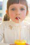 Little girl drinking juice. Portrait of a cute little girl drinking orange juice Royalty Free Stock Photography