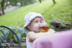 Little girl drinking juice Stock Images
